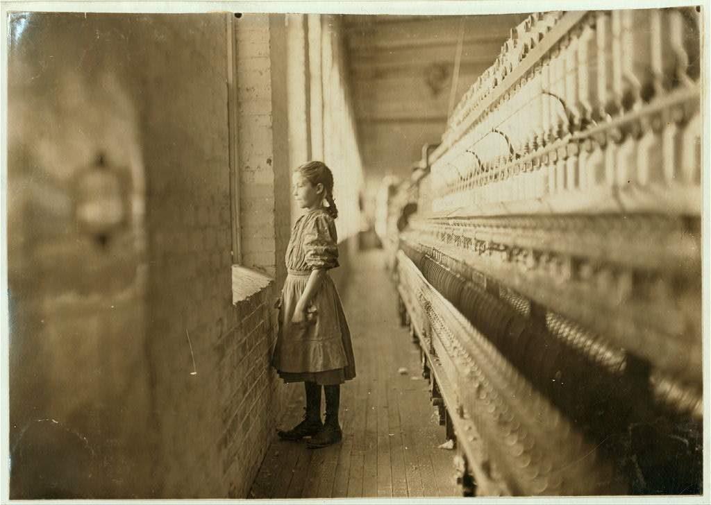 Bambina lavoratrice che guarda fuori dalla finestra