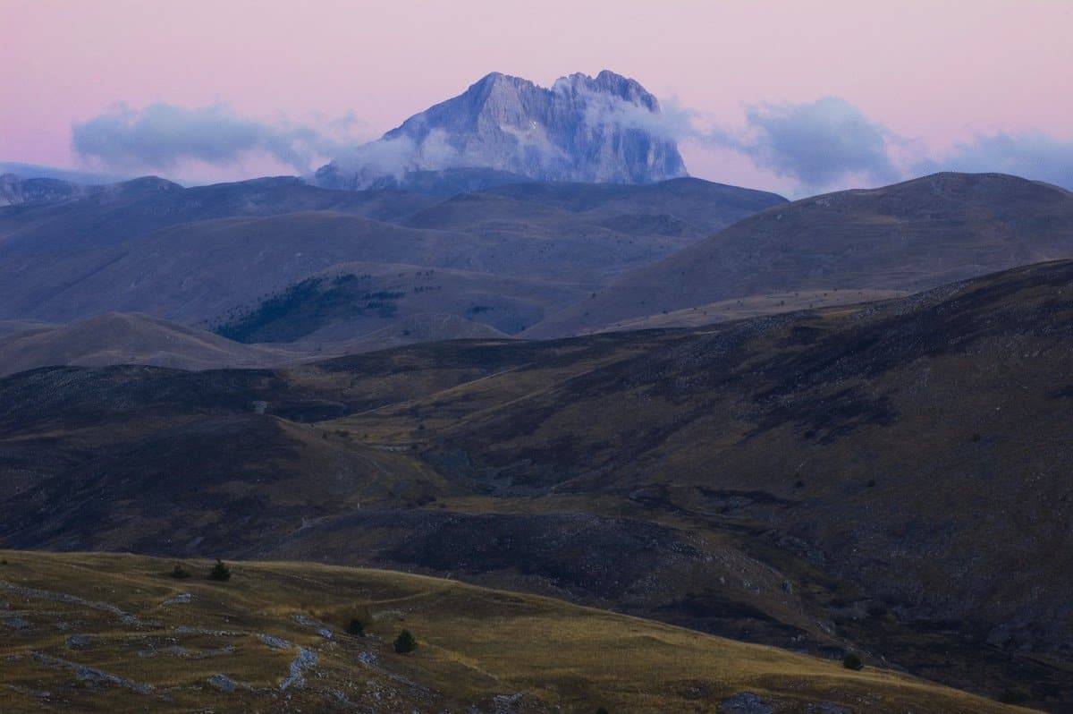 Un picco montagnoso avvolto dalle nubi, dietro una distesa di colline. Una fotografia che evoca mistero e distanza. Di Marco Scataglini