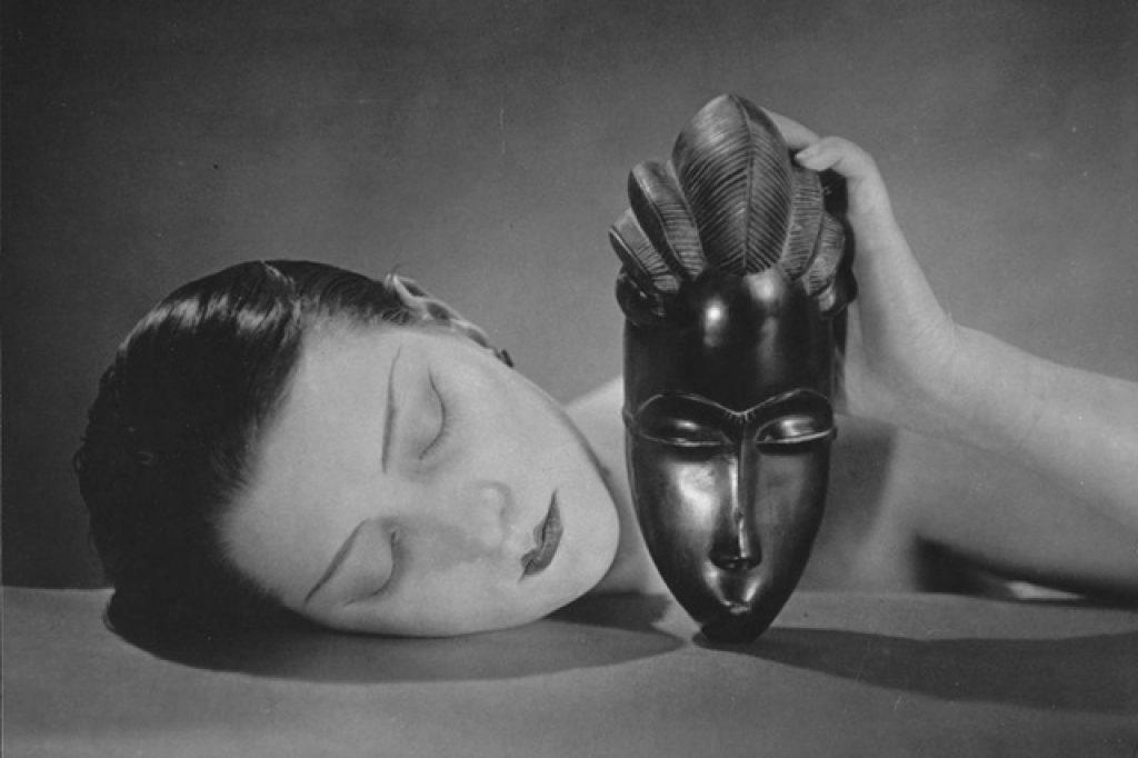 Ritratto di donna con maschera africana. Evidente è il contrasto con la pelle bianca della modella e il nero della maschera